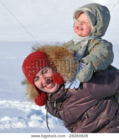 happy family of mother with baby playing in the snow winter park