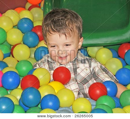 boy in the dry pool with colored balls