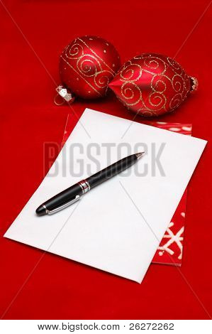 Empty christmas envelope with ornaments, over red background