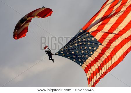 A sky diver carries an American Flag as he descends down through the clouds.