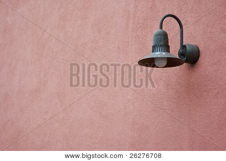 A dirty light fixture on a pink wall