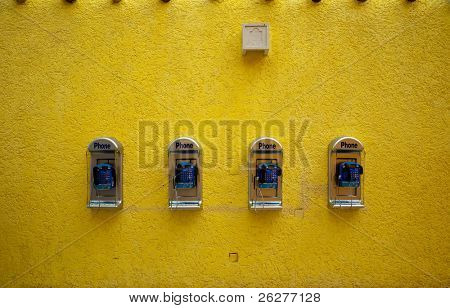 A set of public telephones on a yellow background