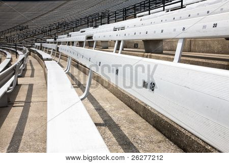 A picture of some empty bleacher seating in rows, taken in a modern school sports stadium facility.