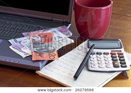 Laptop computer with money from different countries on a desk