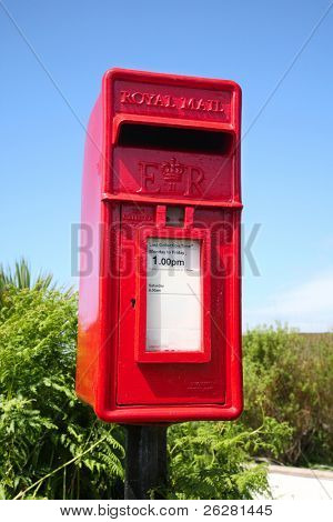 A colorful red small British countryside post box.