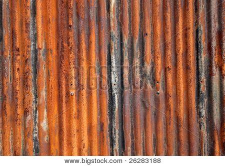 Rusty old corrugated iron fence close up.
