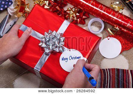 Foto de uma mulher escrevendo feliz Natal em uma marca de presente em um vermelho presente com arco e fita de prata.