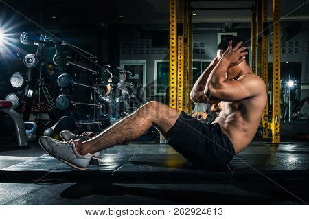 poster of Muscular Guy Doing Sit Ups At Gym With Other People In Background. Young Athlete Doing Stomach Worko