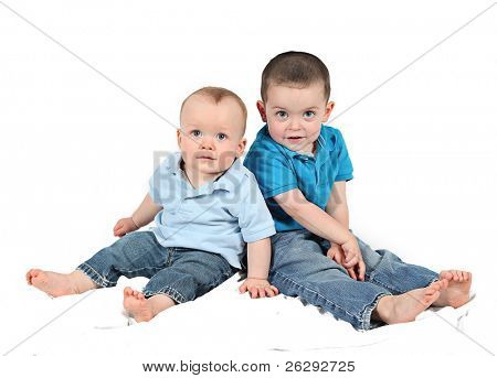 Cute baby boy and brother posing for camera on white background