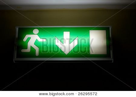 Emergency exit sign glowing green in the dark