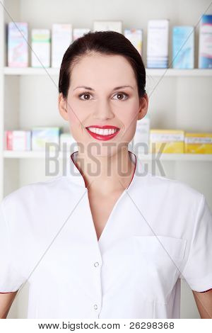 Pretty caucasian smiling pharmacist wearing white uniform.