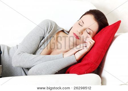 Front view portrait of a young beautiful woman lying on a sofa, being hugged to a red pillow, holding her hands close to the face.