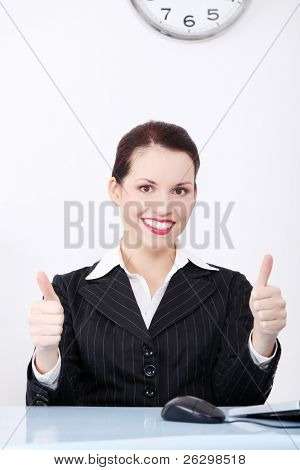 Beautiful caucasian businesswoman gesturing okay sign and sitting behind the desk in the office.
