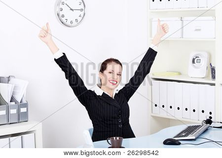 Pretty caucasian businesswoman with hands in the air gesturing okay sign and sitting behind the desk in the office.