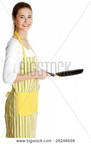 Site view portrait of a young smiling caucasian female teen dressed in apron, holding a frying pan in front of her, on white.