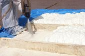 Technician Dressed In A Protective White Uniform Spraying Foam Insulation Using Plural Component Spr poster
