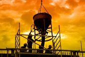 foto of chute  - Silhouettes of construction workers pouring concrete mix at the building site over sunset sky - JPG