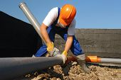 image of sewage  - Plumber assembling pvc sewage pipes in house foundation - JPG