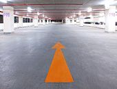 Empty Parking Garage With Yellow Arrow