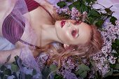 Portrait Of Sexy Blonde In Lingerie With Bright Makeup Lying In Lilac Flower. Slender Blonde, Perfec poster