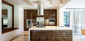 Modern kitchen in wood and marble with island. Nobody inside poster