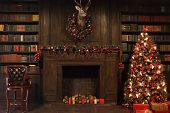 Christmas interior with bookshelves, stuffed deer, wooden fake fireplace, christmas tree, boxes, cha poster