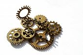 Many Gears Of Brass Are Located On A White Background, One Mounted Above Them poster