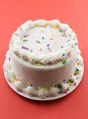 image of birthday-cake  - Birthday cake frosted with white frosting on red background - JPG