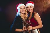 Glamorous Women In Santa Hats Toasting With Champagne Glasses On New Year Party poster