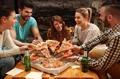 Group of young hungry people taking pieces of big family pizza poster