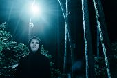 Halloween Concept. Killer Man In White Mask And Black Hood In The Forest Under The Blue Light At Nig poster