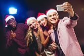 Glamorous Multicultural Friends In Santa Hats Taking Selfie On Smartphone poster