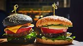 Set Of Homemade Burgers In Black And White Buns With Tomato, Lettuce, Cheese, Onion On Wood Serving  poster