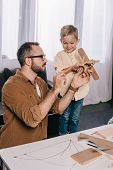 Happy Father And Son Playing With Wooden Plane Model While Modeling At Home poster