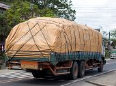stock photo of tarp  - An image of an overloaded truck on a local road - JPG