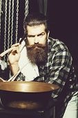 Handsome Bearded Serious Man Hipster With Stylish Haircut And Beard Holding Razor Or Shaver, Stands  poster