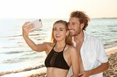 Happy Young Couple In Beachwear Taking Selfie On Seashore poster