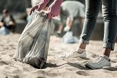 Close Up Of Young Student Wearing Jeans And Sneakers Cleaning Up Trash On The Beach poster
