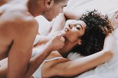 Young Beautiful Couple In Underwear Lying On Bed. Handsome Man Touching Chin Of Attractive Woman. Pa poster