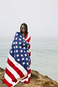 Woman with American Flag. A beautiful woman with an American flag at the beach. red white and blue s poster