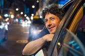 Smiling man looking outside from car window at night. Handsome business man enjoying taxi ride viewi poster