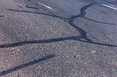 Damaged Road, Cracked Asphalt Sword With Potholes And Spots, Ukraine. Very Bad Asphalt Road With Lar poster