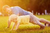 Little Boy And His Father Doing Plank Exercise In Sunny Summer Park. Outdoor Sport Activities For Fa poster