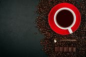 White Cup Of Coffee On The Red Plate With Roasted Coffee Beans, Gold Spoon And Milk Chocolate On The poster