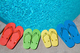 image of swimming pool family  - Colored flipflops of a family of four by the swimming pool - JPG