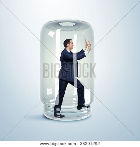 Businessman inside glass jar