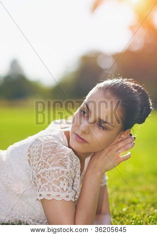 Thoughtful Girl Laying On Grass