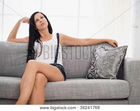 Thoughtful Young Woman Sitting On Couch In Living Room