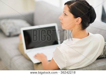 Thoughtful Young Woman Laying On Couch And Using Laptop