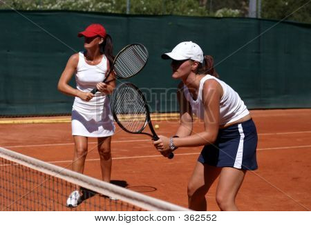Two Fit, Young, Healthy Women Playing Doubles At Tennis In The Sun